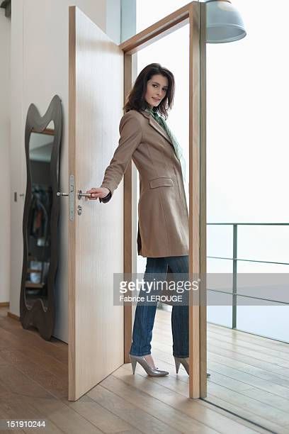 Woman closing the door of a house