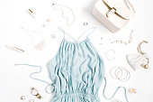 Beauty blog concept. Woman clothes and accessories: blue dress, purse, watches, bracelet, necklace, rings, lipstick on white background. Flat lay, top view trendy fashion feminine background.