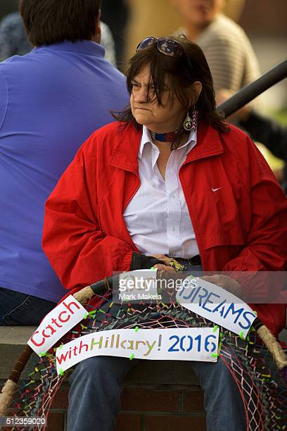 A woman clutching an oversized dreamcatcher stating 'Catch Our Dreams with Hillary 2016' is among a gathering of Hillary Clinton supporters outside...