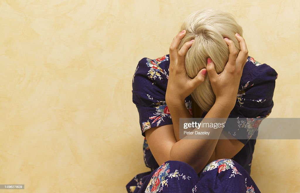 Woman clutching her head in mental anguish