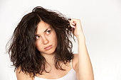 Woman clutching wavy dark hair over a white background