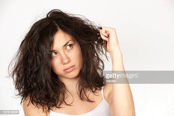 Woman clutching wavy dark hair over a white background