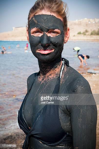 Woman coated in mud at the Dead Sea in Jordan