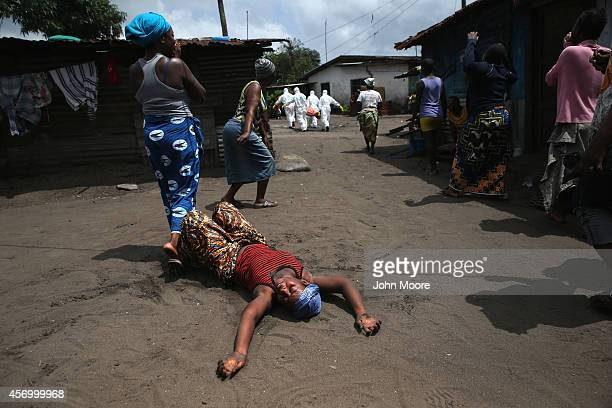 A woman collapses after Ebola burial team members take her sister Mekie Nagbe for cremation on October 10 2014 in Monrovia Liberia Nagbe a market...