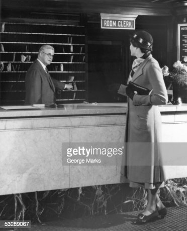 Woman collecting her mail at front desk : Stock Photo