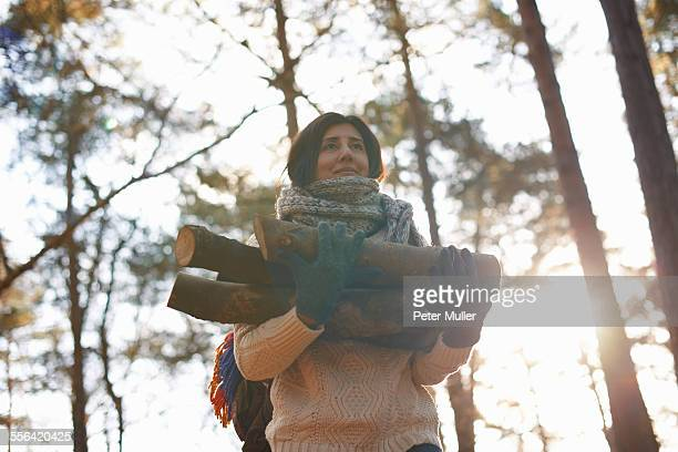 Woman collecting logs for campfire in forest