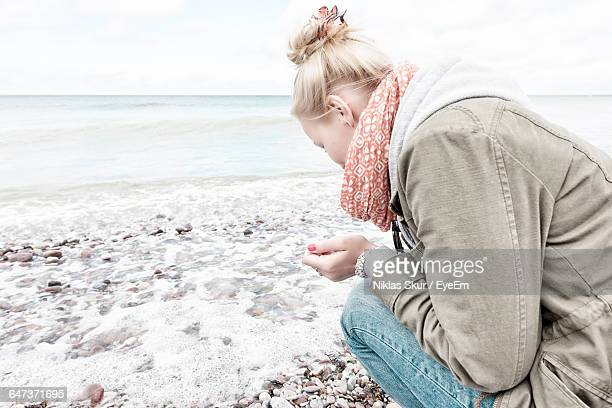 Woman Collecting Pebbles On Shore Against Sky