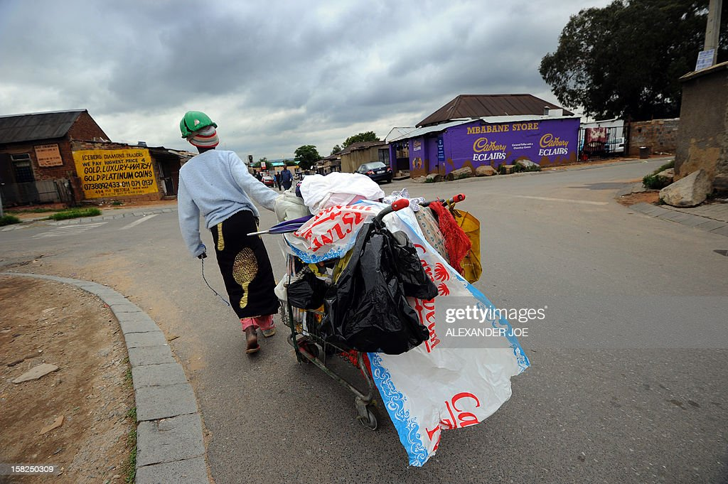 A woman collecting plastic bags carries her cart through the streets of Johannesburg's Alexandra township on December 12, 2012.