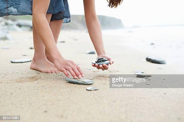 Woman collecting rocks at beach