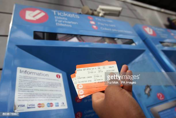 A woman collecting train tickets from a machine at Finsbury Park station in north London as rail passengers will today learn just how much their...