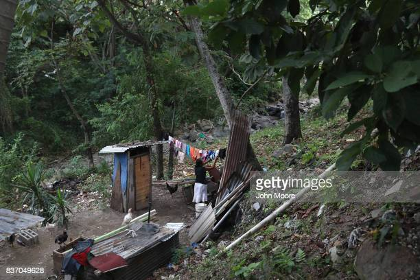 A woman collects dried laundry next to her home's outhouse in an impoverished neighborhood on August 19 2017 in San Pedro Sula Honduras Honduras is...