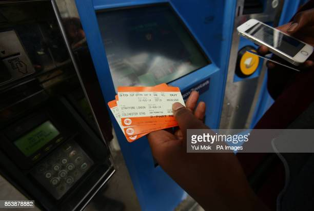 A woman collects her train tickets from a machine at Finsbury Park station in north London as rail passengers will today learn just how much their...