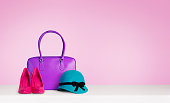Purple leather handbag, red pink high heels, and green hat on white table.