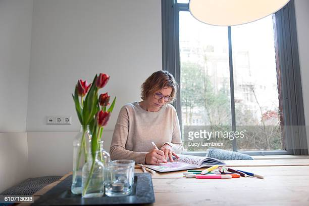 Woman coloring in the kitchen
