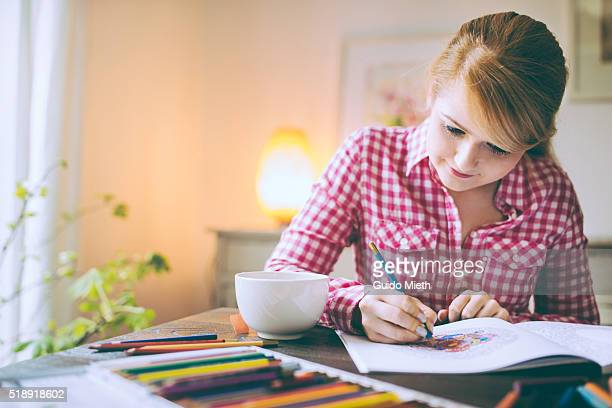 Woman colouring a drawing book.