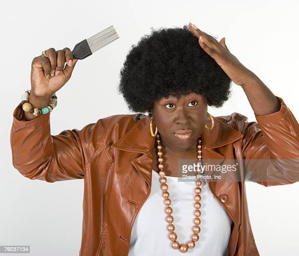 Woman combing afro, against white background