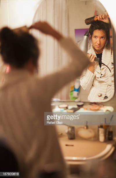 Woman combing and drying her hair