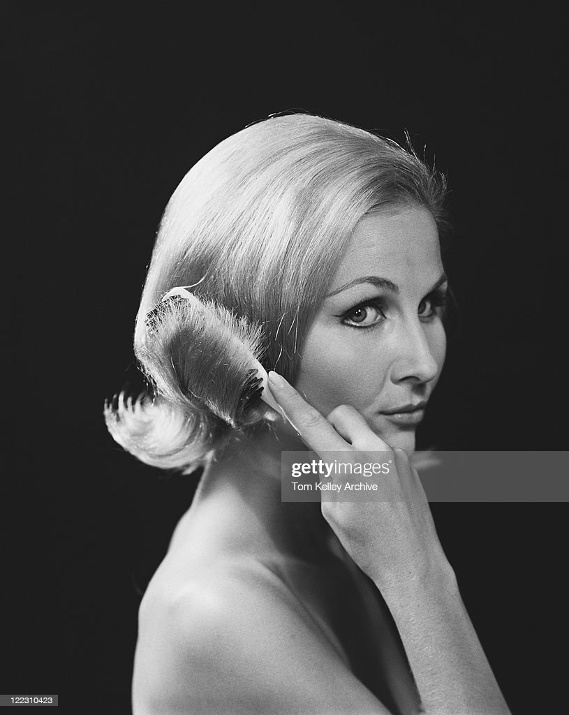 Woman combing hair against black background, close-up : Stock Photo