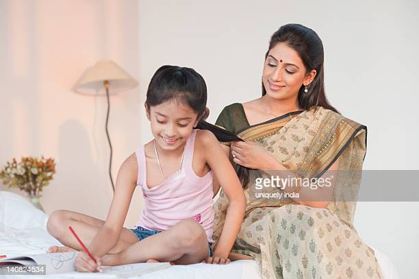 Woman combing hair of her daughter doing homework