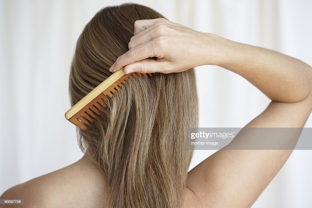 Woman combing hair : Stock Photo