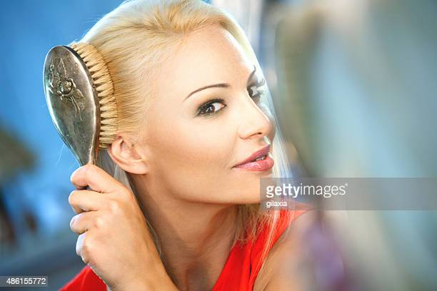 Woman combing her hair in front of a mirror.