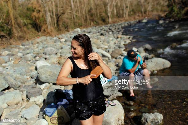A woman combs her hair after taking a bath on the Cuyon River in the aftermath of Hurricane Maria in Coamo Puerto Rico September 29 2017 US military...