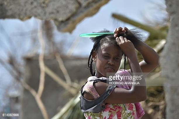 A woman combs her hair in a home destroyed by Hurricane Matthew in Port Salut southwest of PortauPrince on October 11 2016 Haiti faces a humanitarian...