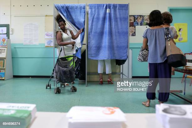 A woman comes out of a voting booth at a polling station in La Possession on the French Indian Ocean island of La Reunion during the first round of...