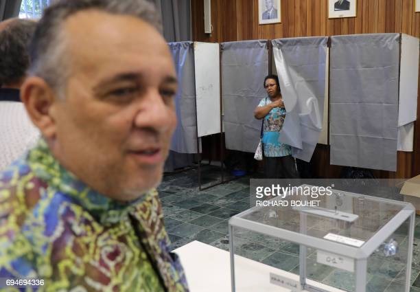 A woman comes out of a voting booth to cast her ballot at a polling station in La Possession on the French Indian Ocean island of La Reunion during...