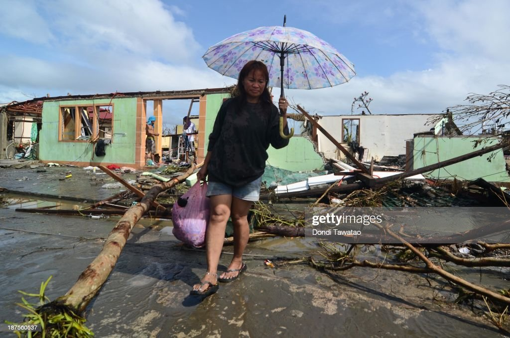 A woman comes out of her damaged house in the aftermath of typhoon Haiyan on November 10 2013 in Tacloban City Leyte Philippines Typhoon Haiyan...