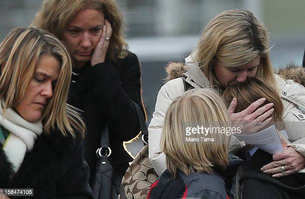 A woman comforts a boy as mourners depart Honan Funeral Home after the funeral for 6yearold Jack Pinto on December 17 2012 in Newtown Connecticut...