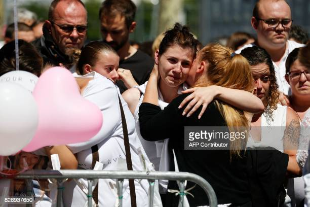 A woman comforts another as she cries in front of a makeshift memorial at the 'Au Cuba Libre' bar on August 6 in Rouen northwestern France in tribute...