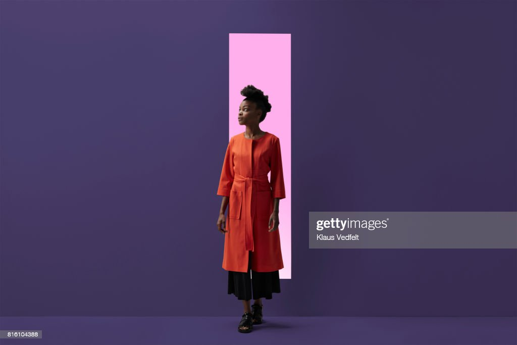 Woman coming out of rectangular opening in coloured wall : Stock Photo