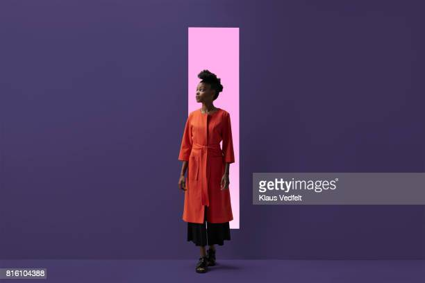 Woman coming out of rectangular opening in coloured wall