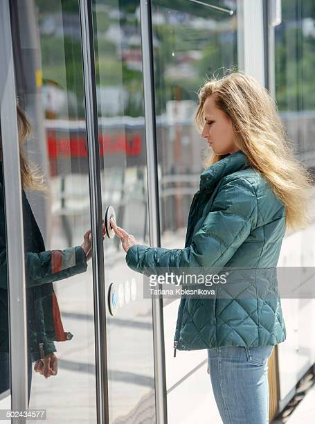 Woman commuter opening the door of a train