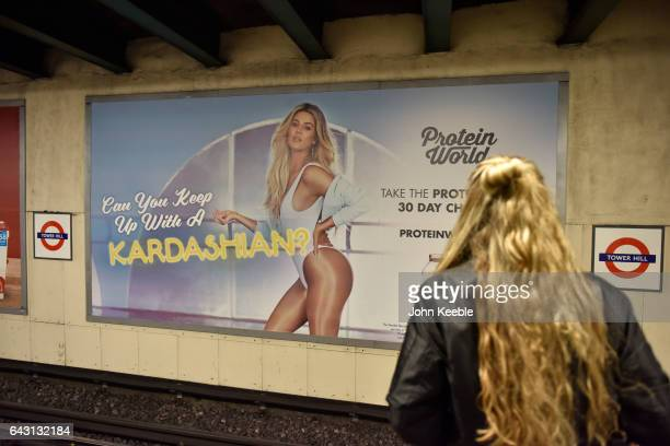 A woman commuter stands on the platform at Tower Hill underground station opposite a Protein World advertising poster featuring Khloe Kardashian on...
