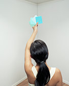 Woman comparing color swatches against wall in room, rear view