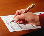 Woman completing loan application, Close-up of hand