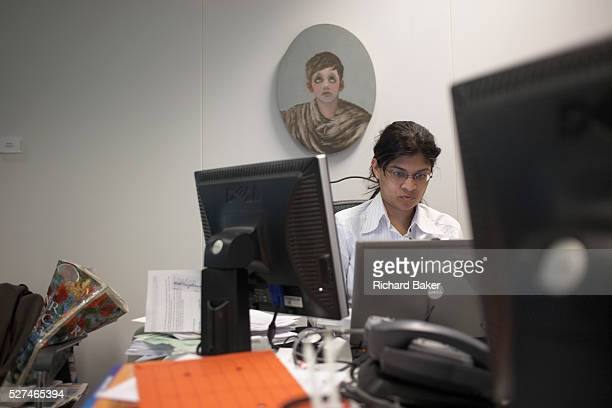 A woman concentrates in a cluttered office unit beneath corporate artwork in Ernst Young's Norman Fosterdesigned building The ovalshaped picture...