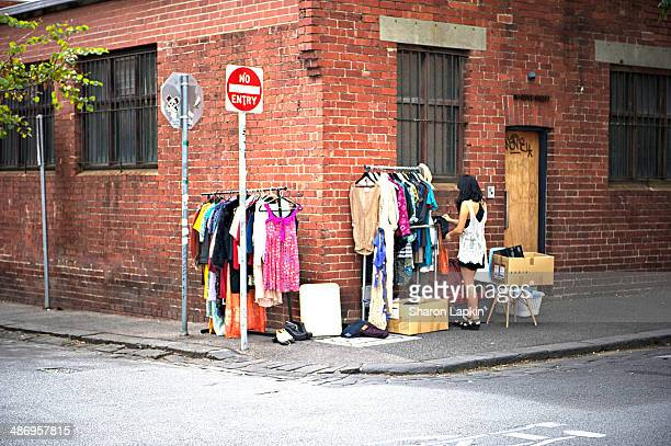 Woman conducting a garage sale on a street corner in Fitzroy Melbourne on a Saturday morning