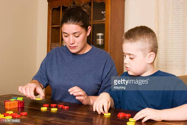 A woman conducting ABA therapy with a young boy at a table