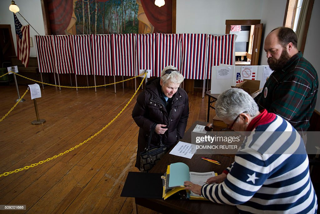 A woman confirms her identity as she casts her ballot, February 9, 2016, in Chichester, New Hampshire. New Hampshire voters headed to polls at the snowy break of day Tuesday for the crucial first US presidential primary, with Donald Trump chasing victory and Hillary Clinton looking to narrow the gap on Bernie Sanders. / AFP / DOMINICK REUTER