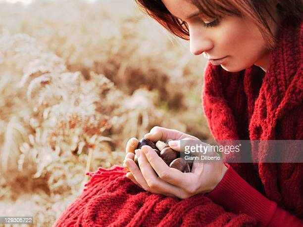 A woman considering a handful of chestnuts she's holding