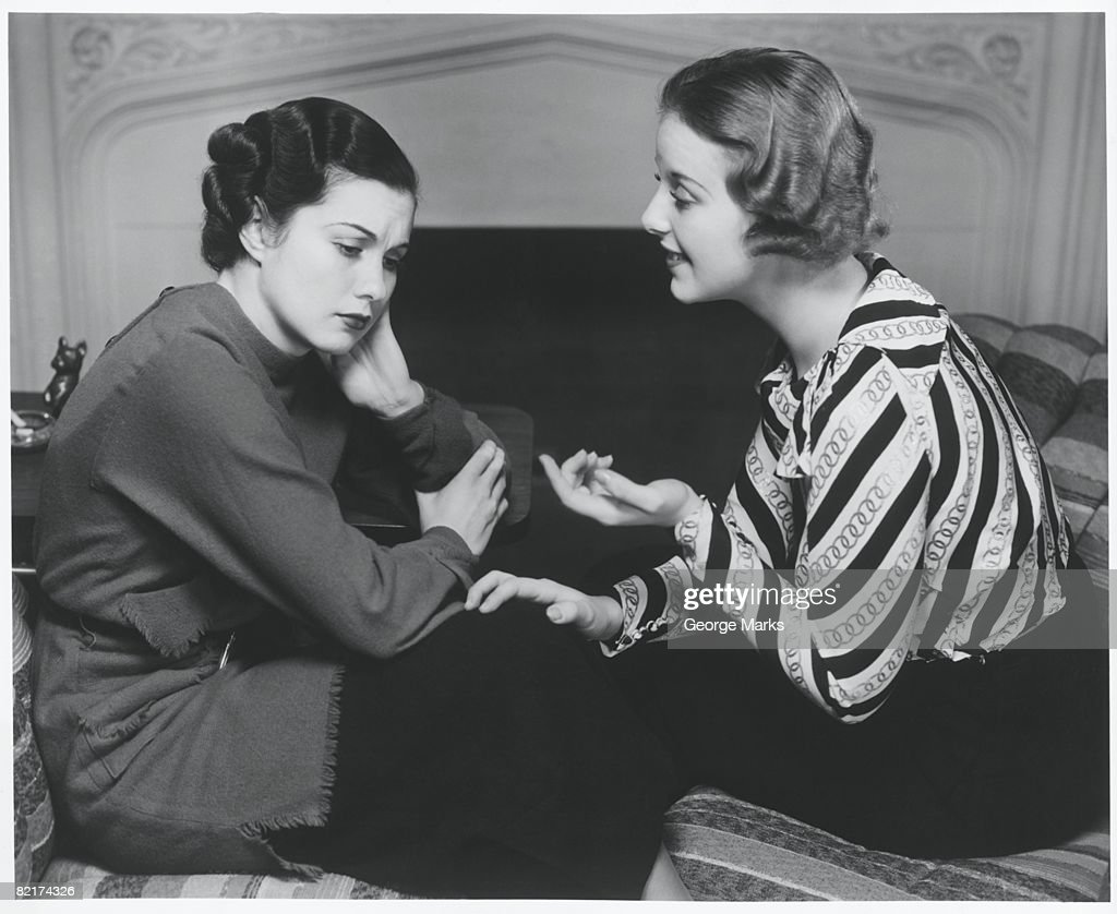 Woman consoling friend at fireplace, (B&W) : Stock Photo