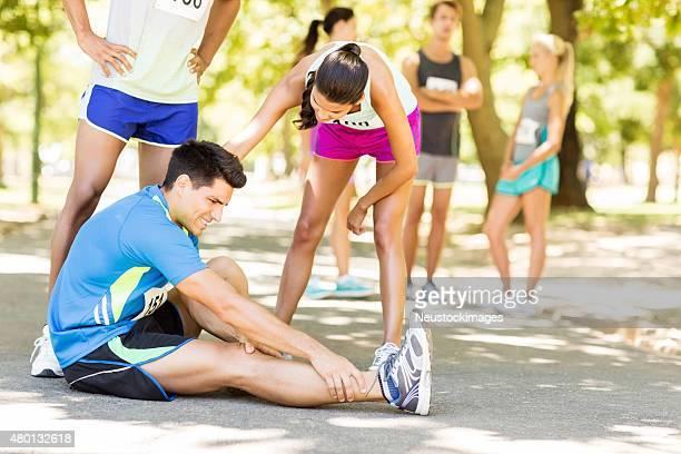 Frau trösten Marathon Läufer leiden Knöchel Schmerzen,