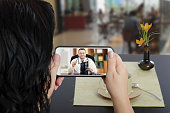 """Woman sits at a cafe table and communicates with telemedicine doctor by cellphone. In touchscreen, male physician reviewing brain x-ray image. """"nPatient has ability to reach telemedicine specialist re"""