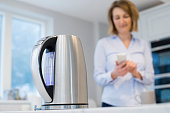 Woman Controlling Smart Kettle Using App On Mobile Phone