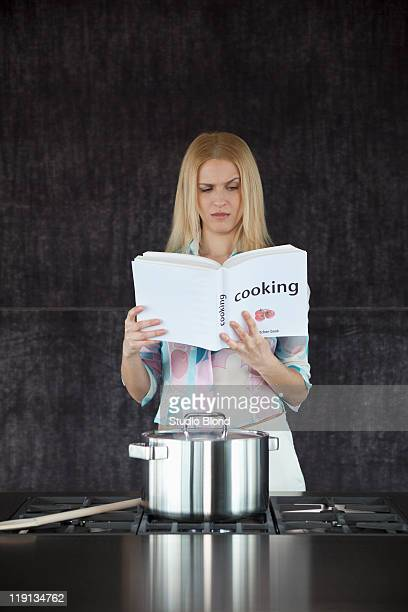 Woman cooking confused by cookery book.