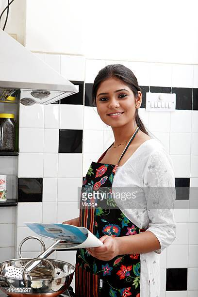 Woman cooking food, recipe book