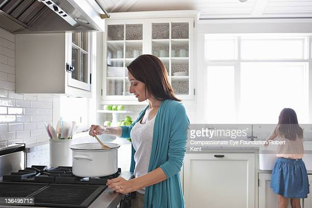 Woman cooking in kitchen, daughter in background